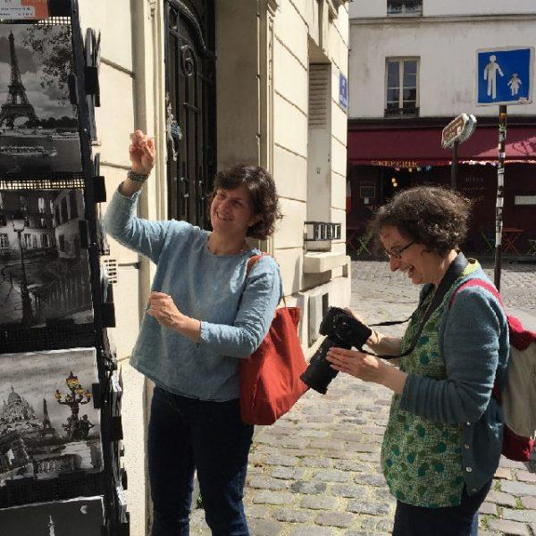 Durant la séance photos, Marie et Raphaële rigolent bien ! Maris fait des photos pendant que Raphaële fait danser le lutin devant les cartes postales touristiques.